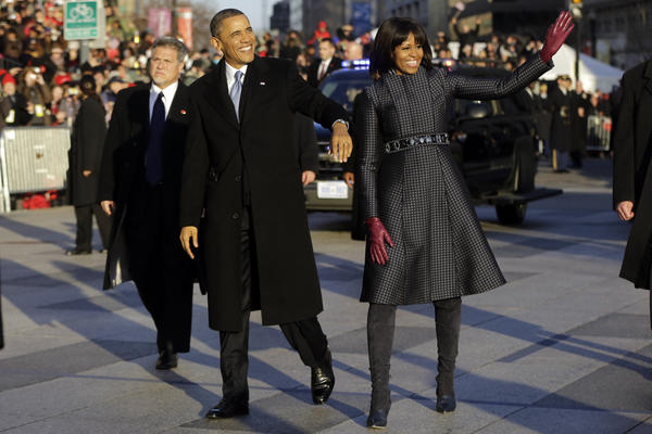 Obama and Michelle walk in the inauguration parade near the White House. The first lady chose a coat by designer Thom Browne.