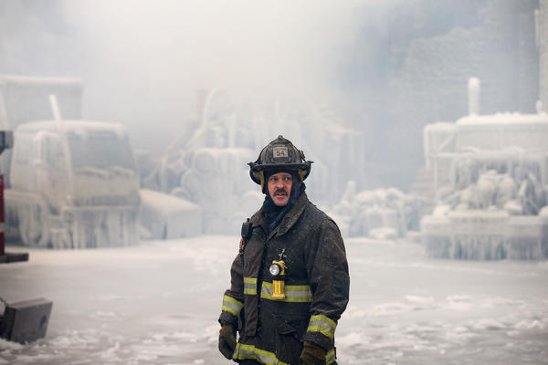 A firefighter helps to extinguish a massive blaze at a vacant warehouse in Chicago.