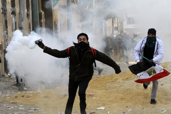 An Egyptian protester runs to throw tear gas during a protest in Tahrir Square on January 25, 2013 in Cairo.