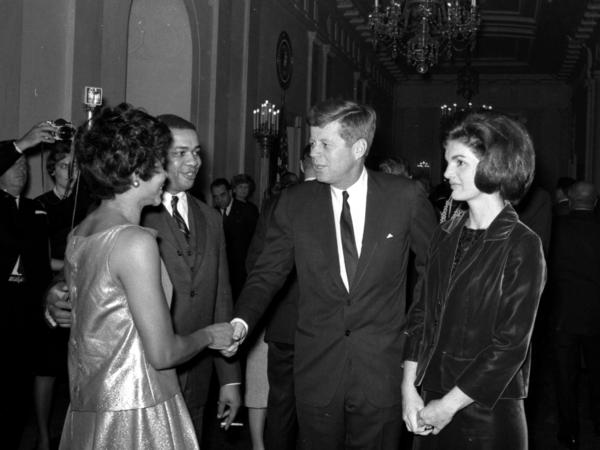 President and Mrs. Kennedy greet Clarence C. Feurgeson Jr., counsel to the Civil Rights Commission, and his wife, at the White House reception.