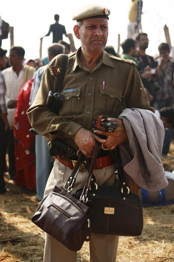 An officer guards the purses of pilgrims who came to pay homage to the holy waters at the confluence of the Ganges, Yamuna and the mythical Saraswati rivers.