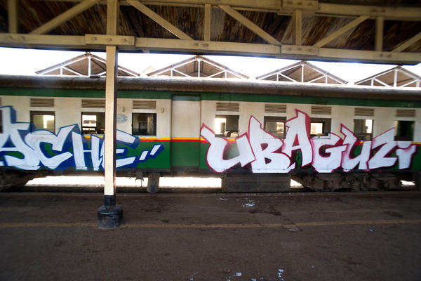 """Tuwache Ubaguzi"" is part of a longer phrase written across the 10-car train, quoting the first line of a poem composed by a 13-year-old girl from Kibera. The full text translates to ""Down with tribalism, down with discrimination, let's live in peace."""