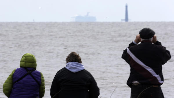 Spectators watch the Carnival cruise ship Triumph near Dauphin Island, Ala., Thursday, as the ship is towed to a terminal in Mobile. The Triumph is expected to arrive late Thursday night.