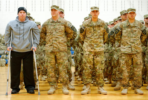 As part of homecoming ceremonies at Joint Base Lewis-McChord in Washington state in January, Army Spc. Tyler Jeffries — with crutches and prosthetic legs — joins his unit in formation as the national anthem is played. The homecoming marked the first time Jeffries had seen his platoon since he lost both his legs in a roadside bombing in Afghanistan last October.