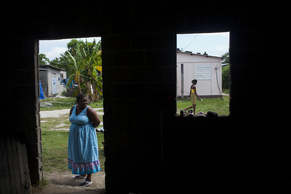 Anatolia Ramirez waits outside the home of one of the HIV-positive women she visits in Sambo Creek. Ramirez is a community health worker who visits people with HIV in order to check up on them, and to offer assistance and support.