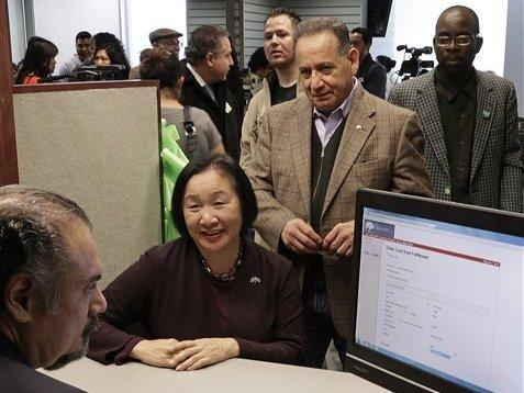 Oakland Mayor Jean Quan (center) and former Oakland Councilman Ignacio De La Fuente are registered for the Oakland City ID Prepaid MasterCard program by Jaime Suriano (left) Feb. 1 in Oakland, Calif.