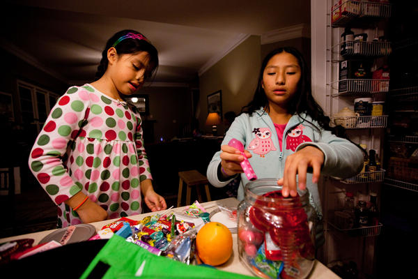 Celedonia (left) and Anita pick a few pieces of candy to add to their lunches. The house rule is that they can eat no more than two to three pieces a day.