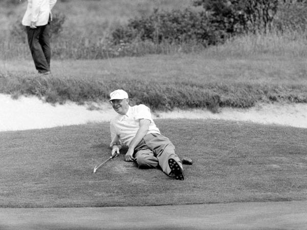 U.S. President Dwight Eisenhower relaxes at the 18th hole during a golf game in Newport, R.I., Sept. 10, 1957.
