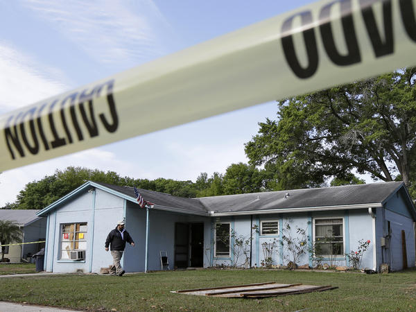 An engineer surveys in front of the home where a sinkhole opened up late Thursday near Tampa, Fla. A man who had been in one of the home's bedrooms screamed for help and disappeared. It's feared he died.