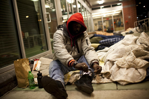 Albert Monroe and many others sleep on the porch and under the bright lights of the HCH clinic. Many say it's safer than sleeping under the highway or in city shelters, where theft and violence aren't uncommon.