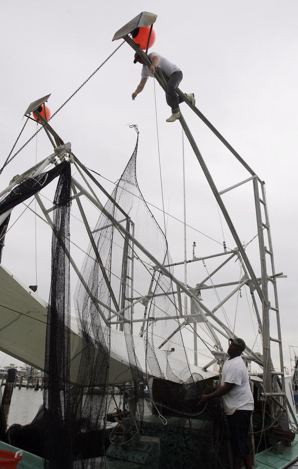 John Berthelot, top, and Hosea Wilson, bottom right, release the nets from their shrimp boat, Monday, May 3, 2010, at the Venice Marina in Venice, La.