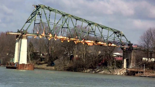 An image taken from a video depicts a section of the Dick Henderson Memorial Bridge in Nitro, WV, being demolished by a controlled explosion Friday.