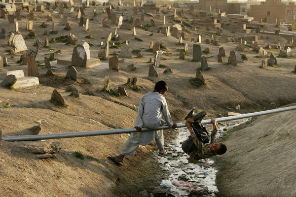 Boys play on a water pipe in a cemetery in Kabul, 2007.