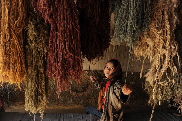 Ten-year-old Nahid grabs a thread while weaving carpet in her home in Kabul, 2010. Carpets, made mostly in the country's north, are one of Afghanistan's few major exports.