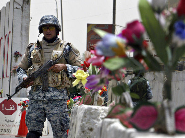 An Iraqi policeman stands guard at a checkpoint decorated with plastic flowers in Baghdad in 2008.