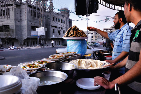 "Two men sell foods on the street. In Gaza, home foods are ""almost exclusively prepared by women,"" the authors write. Restaurant food, they write, ""is nearly always prepared by men."""