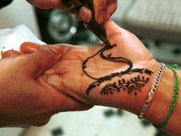 Hairdresser Paramjit Kaur paints a traditional Indian henna design on a client's hand in Kent, Wash.