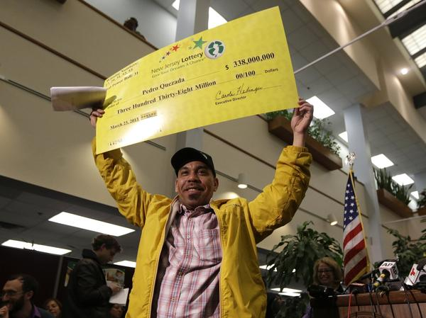 Powerball winner Pedro Quezada holds up a promotional check featuring his $338 million jackpot. He owes $29,000 in back child support payments, according to New Jersey law enforcement authorities.