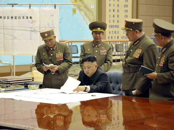 """North Korean leader Kim Jong Un with top brass in a photo released by the state-run KCNA. The chart in the background reportedly reads """"U.S. mainland strike plan""""."""