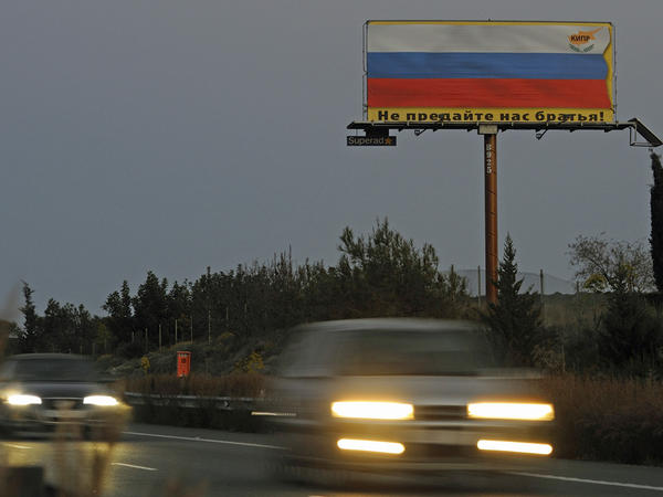"A Cypriot business association has erected a billboard that reads, in Russian, ""Do not betray us, brothers,"" over a Russian flag. Many Cypriots expect Russians will flee in the face of a eurozone deal."