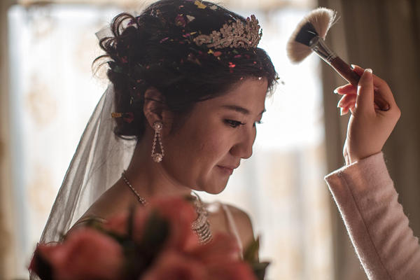 Lucy Wang gets her makeup touched up before her wedding ceremony at a Beijing restaurant. Wang is marrying Derek Wei, who paid her family more than $10,000 for her bride price.