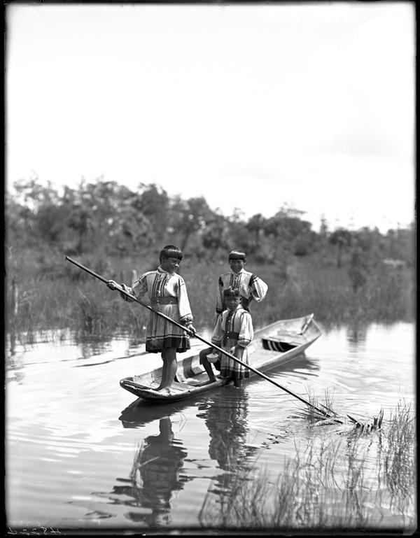 Boys play in a canoe.