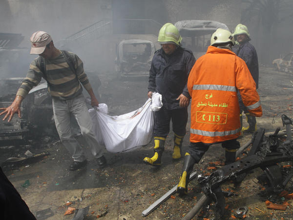 Rescue teams recover bodies from the scene of Monday's car bomb explosion in Damascus. Syria's state television reported that intense gunfire followed the blast.