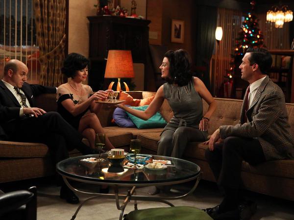Dr. Arnold Rosen (Brian Markinson) and Sylvia Rosen (Linda Cardellini) celebrate New Year's Eve with Megan Draper (Jessica Pare) and Don Draper (Jon Hamm) as the sixth season of <em>Mad Men</em> opens.