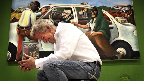 """Author Benjamin Alire Saenz writes about life on the U.S.-Mexico border. Here he holds his latest book, <em>Everything Begins and Ends at the Kentucky Club</em>, in front of """"$26,"""" a painting by Francisco Delgado (the presidents in the painting appear on American bills worth a collective $26)."""