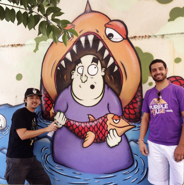 Artist Guilherme Matsumoto (left) painted this mural on the wall of Walter Orsati's Purple House Hostel in Sao Paulo. The two were matched up by the Color+City urban art project.