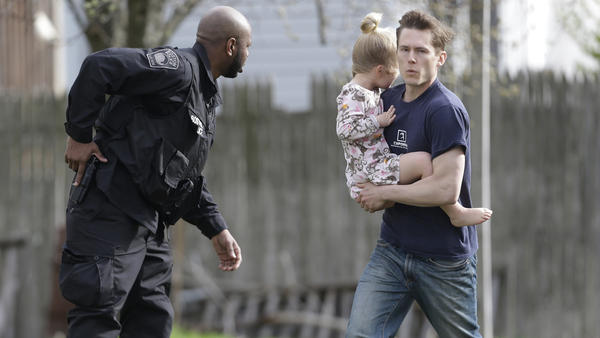 A police officer evacuates a shoeless man holding a child as members of law enforcement conduct a search for a suspect in the Boston Marathon bombings in Watertown, Mass., on Friday.