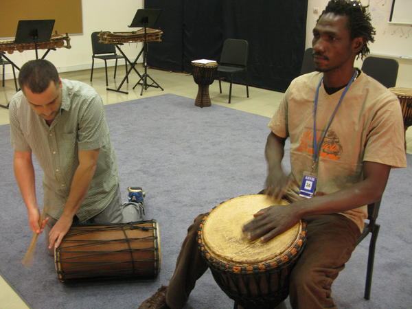 Teacher Paul Chandler (left) and musician Siaka Doumbia play <em>djembe</em> drums during music class.