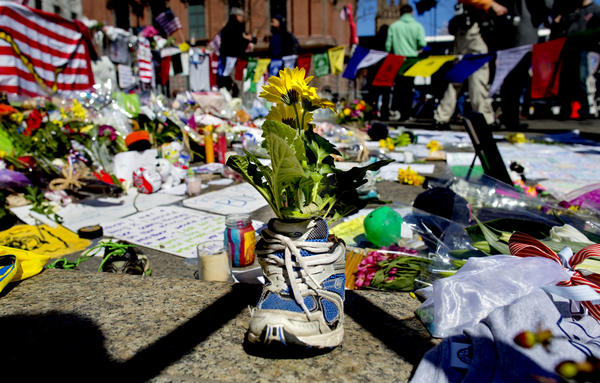 A memento of flowers in a running shoe rests at a makeshift memorial in Boston's Back Bay neighborhood on Thursday.