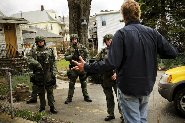 Members of a police SWAT team talk to a man while conducting their search  on Thursday.