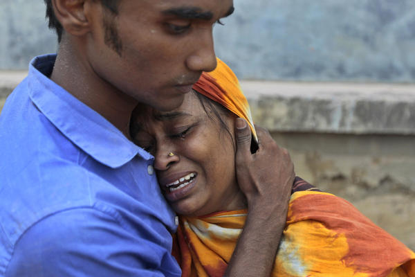 Relatives mourn a victim at the site of the building collapse.