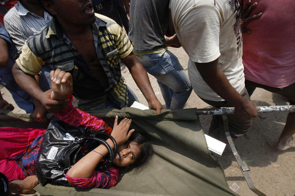 Civilians rescue an injured garment worker during a rescue operation.
