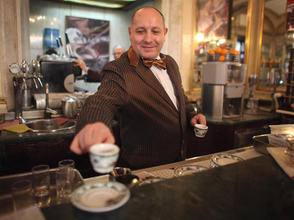 A barista serves coffee at a cafe in Naples, Italy. The Italian city's long-standing tradition of buying a cup for a less-fortunate stranger is now spreading across Europe.
