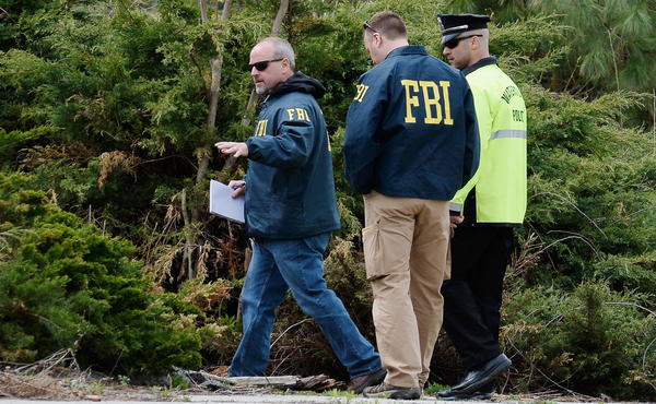 Last week, FBI investigators and a Watertown, Mass., police officer investigate the scene near the boat where bombing suspect Dzhokhar Tsarnaev was hiding. Democrats have argued that the way the government responded to the Boston attacks makes a case for not cutting too deeply.