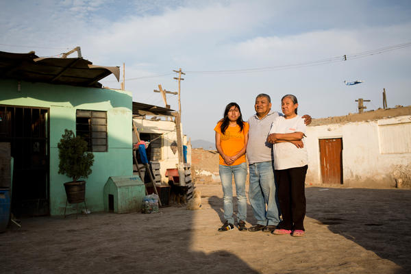 Manuel Chira Juarez and Maria Medina de Chira stand on the dirt road outside their home with their daughter Jenny Chira Medina as an airplane passes by overhead. Residents say that after decades of living so close to the airport, they don't hear the noise of the planes overhead and continue their conversations with slightly raised voices as the planes pass.