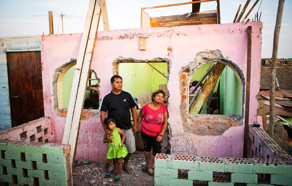 Ricardo Galvez, Giovanna Meneses Pisco and Arely Betzabe pose for a photograph in front of their former home El Ayllu. The family was back in the neighborhood to gather some of their belongings, and Giovanna spent the hours teary-eyed. As soon as families moved out, the Ministry of Transportation and Communications, with the help of paid community members, began to demolish the buildings.