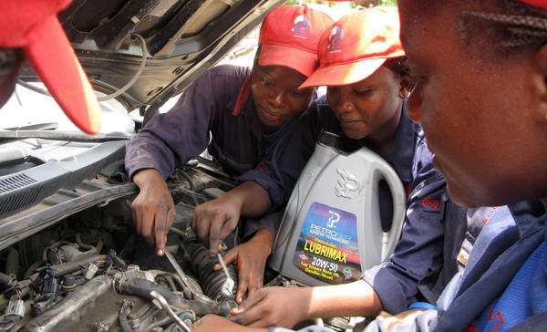 Students at the Lady Mechanic Initiative in Lagos, Nigeria, work on cars in their open air workshop.