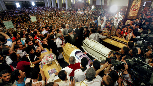 Egyptian Christians gather around four coffins during a funeral service at the Saint Mark Coptic cathedral in Cairo on April 7. Religious violence this month has killed three Muslims and at least six Christians.