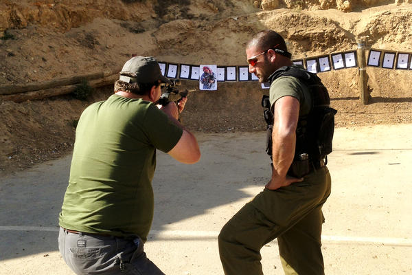 A tourist commando gets one-on-one instruction during target practice.