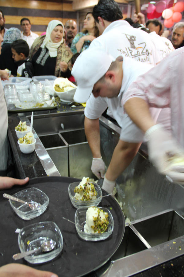 Employees scoop ice cream, which is topped with pistachios, at Bakdash's opening in Amman, Jordan, this week. Bakdash has been a landmark in Damascus, Syria, since 1895. But the war there has made it hard to get supplies, so the owners have set up a new shop in Amman.