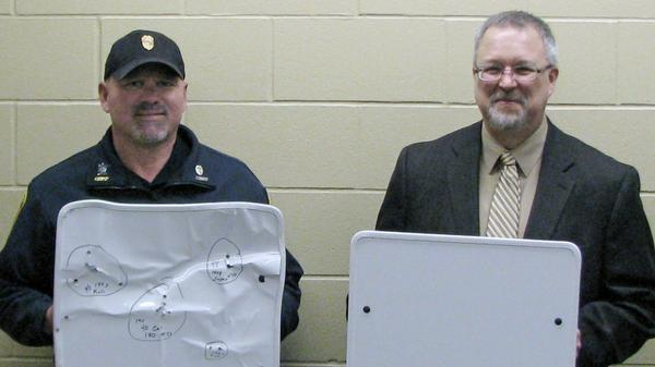 Cold Spring, Minn., Police Chief Phil Jones (left) and Rocori School District Superintendent Scott Staska hold bulletproof whiteboards in April while announcing the school system's $25,000 investment in the shields.