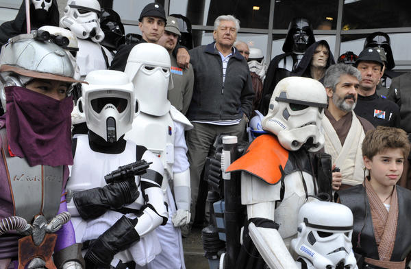 Fans are celebrating Star Wars Day today, May 4. Here, actor David Prowse (center),  who played Darth Vader in the first <em>Star Wars</em> trilogy, poses with costumed fans in France last week.