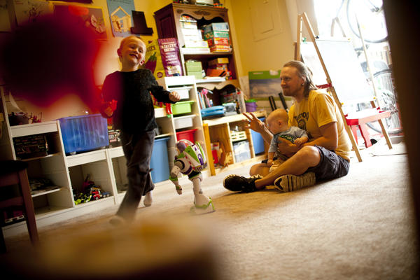 Jonathan holds Zane while Egan runs in the family's playroom.