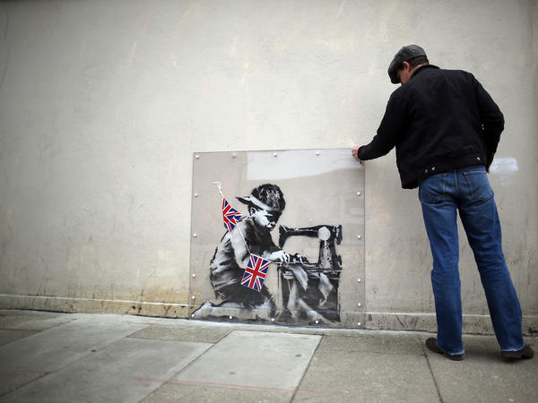 A man inspects a plastic cover placed over <em>Slave Labour</em>, an artwork attributed to Banksy, in London. This piece of art was put up for sale in Miami last February, but the ensuing outrage led to the auction's cancellation. The mural is now part of an exhibition in London, and is is expected to move to the U.S. afterward.