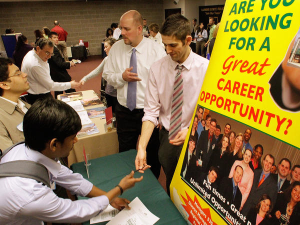 Students fill out applications during a job fair at the University of Illinois Springfield in February. Fed up with working for free, some interns are suing their employers.