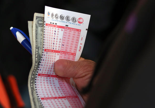 A customer holds a Powerball ticket and money as he waits in line on May 17, 2013 in San Francisco, Calif.